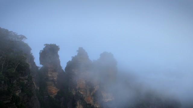 The Three Sisters in the Blue Mountains peek through the fog in a graded timelapse frame.